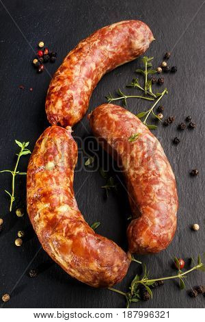 smoked sausage with fresh thyme and peppercorn on slate