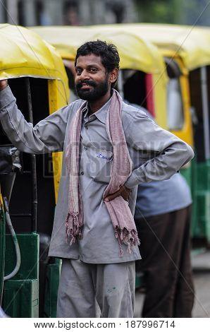 Delhi India september 2 2010: Indian ricksaw tuk tuk man standing next to his tuk tuk.