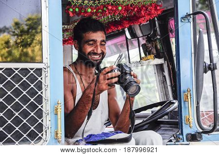 Amritsar India september 5 2010: Indian truck driver watching a picture on a camera.