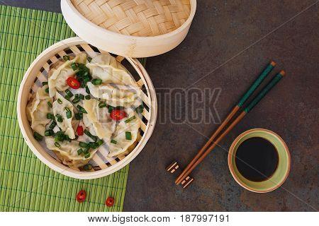 Steamed Chinese dumplings  in bamboo steaming basket . Top view, blank space