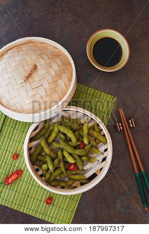 Edamame soybeans served warm with salt in bamboo steamer. Top view, blank space