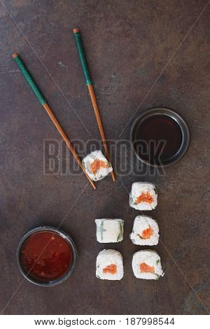Vietnamese rice paper rolls served with soy and chili sauce. Top view, blank space, dark toned image