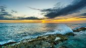 Sunset over the horizon with a few clouds and waves crashing on the rocky shores of the west coast of the tropical Hawaiian island of Oahu poster