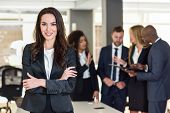 Businesswoman leader looking at camera in modern office with multi-ethnic businesspeople working at the background. Teamwork concept. Caucasian woman. poster
