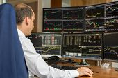 Rear view of stock trader looking and analyzing stock data at multiple computer screens. poster
