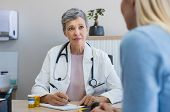 Senior female doctor listening to patient explaining her painful in her office. Mature woman doctor consulting patient in hospital room. Doctor and patient discussing health issue in office. poster