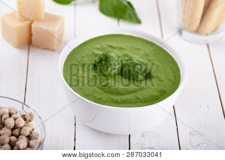 Green Cream Soup Of Spinach And Chickpeas On Concrete Wood Background