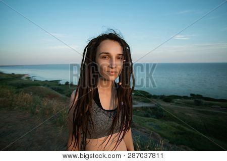 Disheveled Girl With Dreadlocks On A Mountain Overlooking The Sea