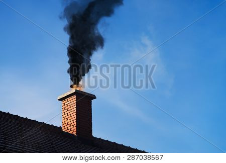 Chimney On Fire With A Black Smoke Coming Out.