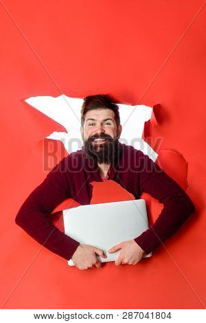 Bearded Man Through Hole In Paper Holds Laptop. Smiling Man Making Hole In Paper With Laptop. Man Wi