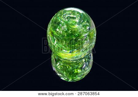 Vibrant Green Glass Sphere And Reflection Isolated Against Black