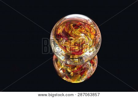Vibrant Colored Glass Sphere And Reflection Isolated Against Black