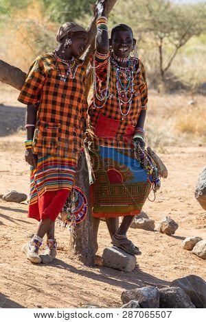 Amboseli, Kenya - 18 February 2019: Two Maasai women sell beadwork souvenirs to tourists at the Iremito gate of Amboseli National Park, Kenya.