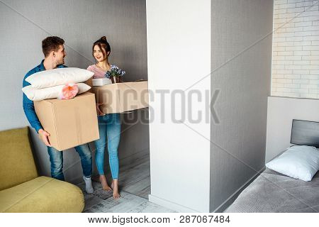 Young Family Couple Bought Or Rented Their First Small Apartment. Happy Excited People Look At Each