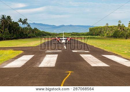 Air Travel In Fiji, Melanesia, Oceania. A Small Propeller Airplane Just Landed To A Remote Airstrip
