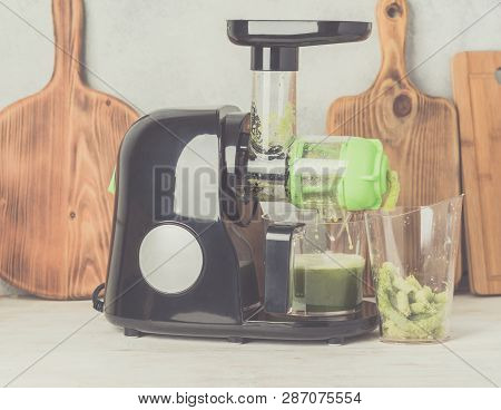 Slow masticating juicer producing healthy celery juice, extracting the pulp, on white table, healthy detox concept, selective focus poster