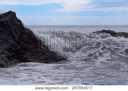 Waves Breaking On The Rock Against Blue Cloudy Sky At Horizon. Portuguese Island Of Madeira