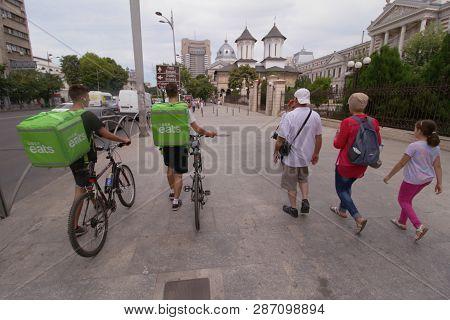 Bucharest, Romania - August 15, 2018: Two Uber Eats Couriers Walk Down The Street On The Sidewalk Ne