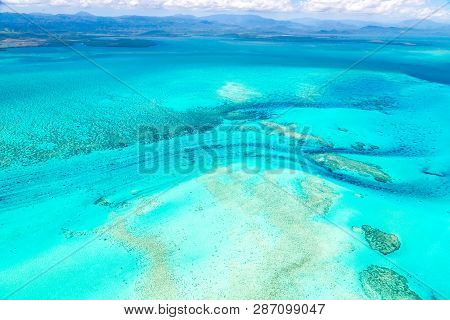 Aerial View Of Idyllic Azure Turquoise Blue Lagoon Of West Coast Barrier Reef, With Mountains Far In