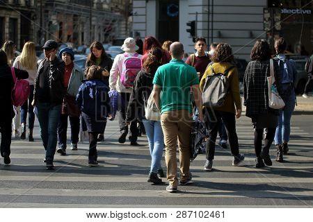 Bucharest, Romania - October 10, 2018: Pedestrians Cross The Street On Nicolae Balcescu Boulevard In