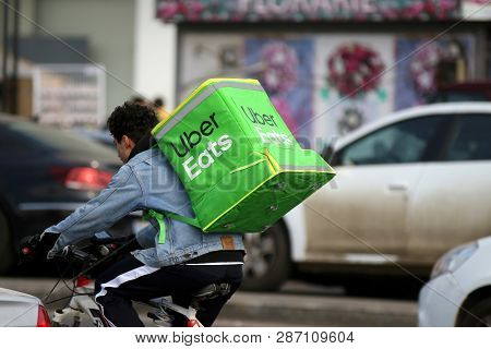 Bucharest, Romania - February 01, 2019: An Uber Eats Food Delivery Courier Delivers Food In Buchares