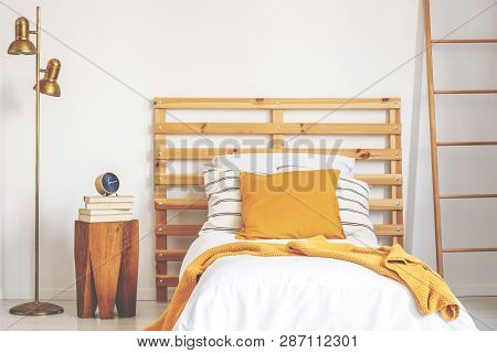 Yellow Pillow And Blanket On White Wooden Single Bed In Natural Bedroom, Real Photo