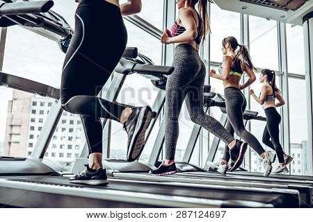 Running Together. Side View Of Young Beautiful Women Looking Away While Running On Treadmill At Gym.