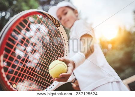 Sporty Little Girl Preparing To Serve Tennis Ball. Close Up Of Beautiful Yong Girl Holding Tennis Ba