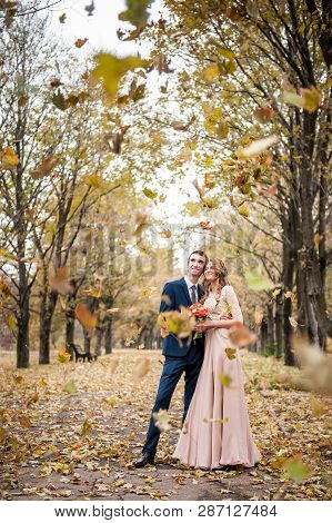 Smilng Newlyweds Hug Under A Fall Of Autumn Leaves.