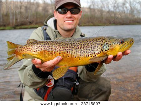Fisherman holding large trout - Fly fishing