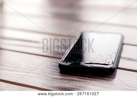 Сloseup Black Smartphone With Broken Screen Glass Lying On Wooden Table. Concept Of Dropping Phone,