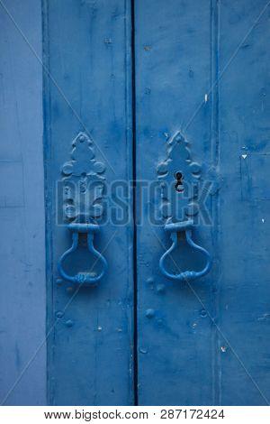Door knockers on the blue door in Lisbon, Portugal.