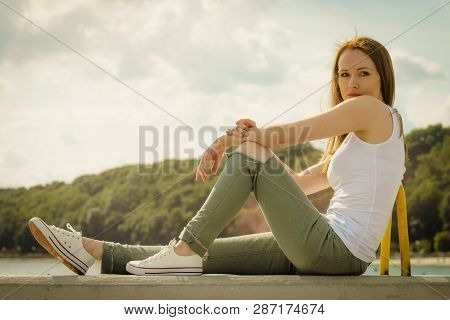 Young Pretty Fashion Model Woman Sitting On Concrete Wall Wearing White Tank Top And Olive Green Tro