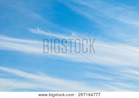 Sky background. Blue sky landscape with dramatic sunset clouds lit by evening sunset light - evening sky view. Colorful sky landscape