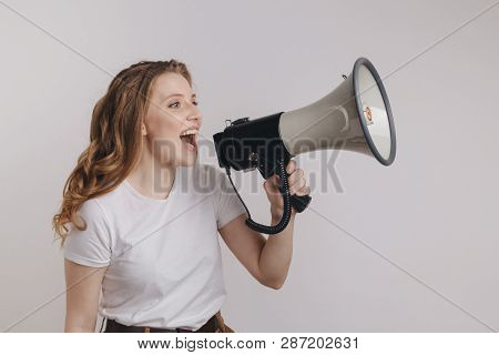 Picture Of Nice Young Woman In A White T-shurt Screaming Into Megaphone In Her Left Hand.
