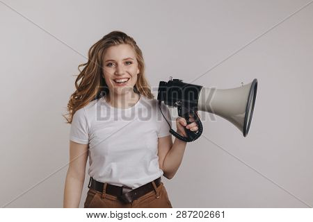 Pretty Curly Hair Model In A White T-shurt Holding Megaphonecand Smiling Isolated Over The White Bac
