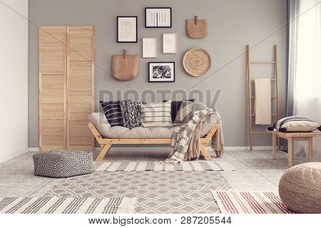 poster of Stylish living room interior design with scandinavian settee, grey wall and natural accents