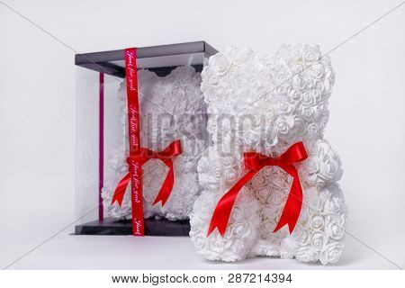 White Teddy Bear Toy Of Foamirane Roses. The Same Teddy In Clear Box With Black Paper Cover On Backg