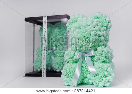 Green Teddy Bear Toy Of Foamirane Roses. The Same Teddy In Clear Box With Black Paper Cover On Backg