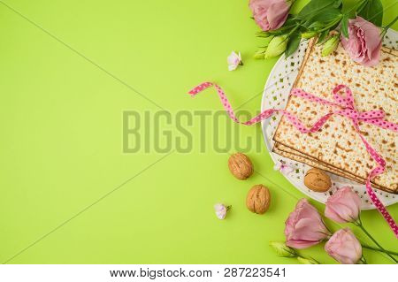 Jewish Holiday Passover Background With Matzo, Seder Plate And Spring Flowers. Top View From Above.