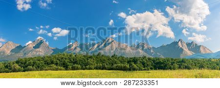 Beautiful Sunny Day In Mountainous Countryside. Row Of Trees Behind The Field. High Tatra Mountain R