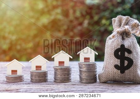 poster of Real estate investment, home loan, mortgage, housing concept. House model on stack of coins and US dollar money bag, Depicts saving and money management for house buying or home repay debt in future.