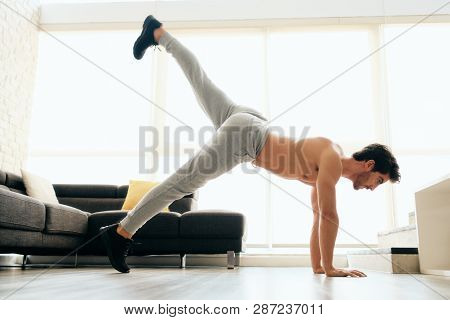 Man Training Legs And Back Muscles Doing Plank With Leg Lift