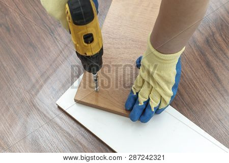 is the process of assembling furniture from chipboard. in the hands of a rechargeable screwdriver for tightening screws poster