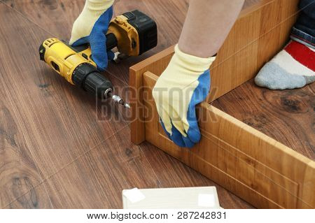 Is The Process Of Assembling Furniture From Chipboard. In The Hands Of A Rechargeable Screwdriver Fo