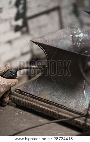 Close Up Of A Hand Of Blacksmith Soldering A Metal Plate In Workshop Vertical Shot. The Blacksmith I