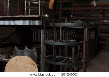 Veritcal Row Of Metal Chairs In Blacksmith Workshop. Handmade Metal Constructions In Blacksmith Work