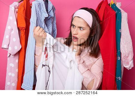 Beautiful Young Woman Near Rack With Hangers. Shocked Lady Finds Awful Stain On White Blouse. Brunet