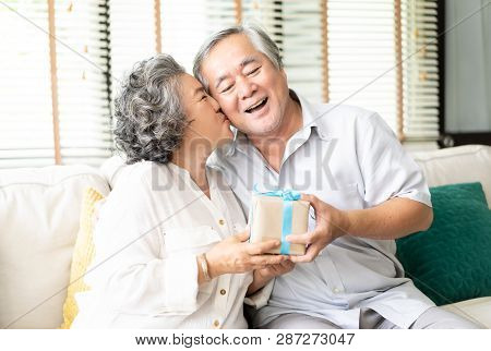 Happy Asian Senior Couple Having Anniversary Day, Bearded Husband Presenting A Packing Gift And Wife