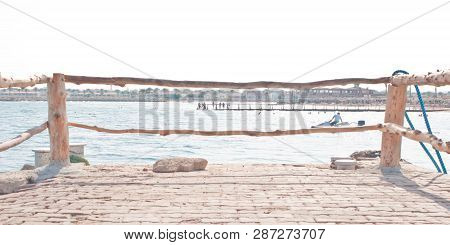 Pier With A Bright Blue Fence In Perspective. Big Red Lighthouse On The Lake Michigan. Bright Blue F
